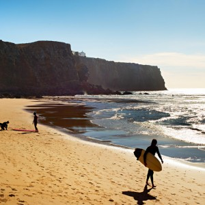 Surfer on the beach in the sunshine day. Portugal